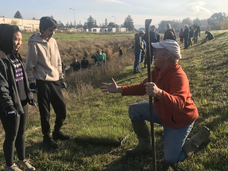 John Zentner training volunteers on how to plant native grass plugs